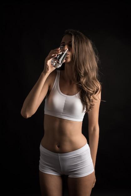 Weibliches eignungsmodell, das ein wasserglas hält Kostenlose Fotos