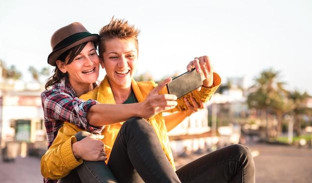 Weibliches freundschaftskonzept mit mädchenpaar, das selfie im freien auf teneriffa nimmt Premium Fotos