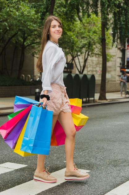 Weibliches gehen mit einkaufstaschen Kostenlose Fotos