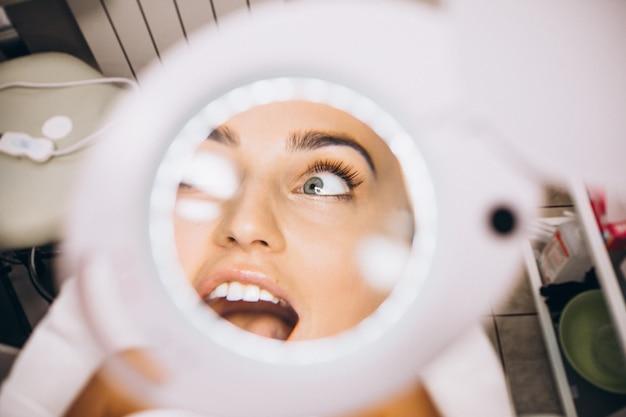 Weibliches gesicht durch die lupe in einem schönheitssalon Kostenlose Fotos
