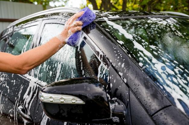 Weibliches handwaschautomobil an der manuellen autowaschselbstbedienungsstation Premium Fotos