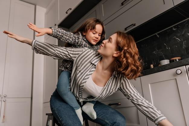 Weibliches kind sitzt bei müttern zurück und spielt mit ihr wie flugzeug in der küche. Kostenlose Fotos