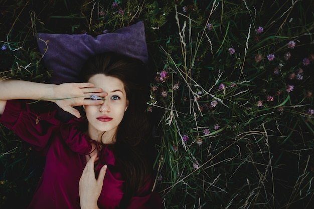 Weibliches porträt. hübsche frau in violettem hemd liegt auf der grünen wiese Kostenlose Fotos