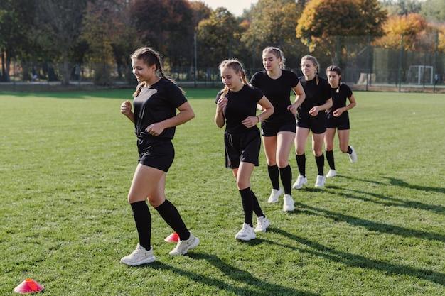 weibliches rugbyteam das durch kegel l uft kostenlose foto