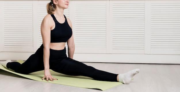 Weibliches training der nahaufnahme zu hause auf matte Kostenlose Fotos