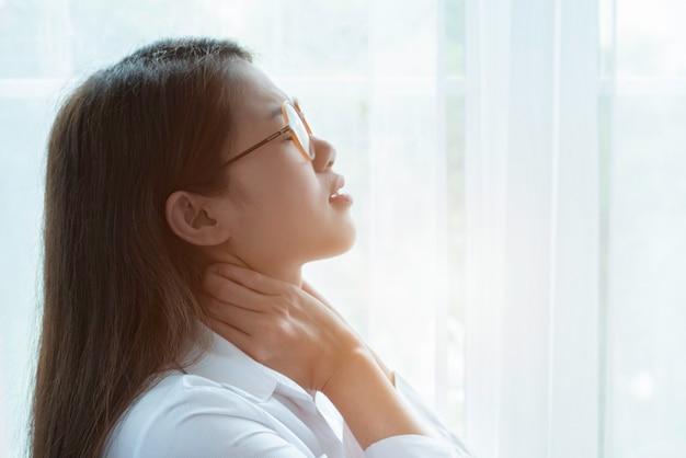 Weichzeichnung der jungen geschäftsfrau mit den brillen, die erschöpft sich fühlen und unter nackenschmerzen leiden Premium Fotos