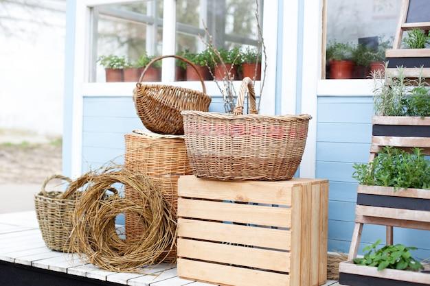 Weidenkörbe neben der gartenausstattung an der wand eines blauen landhauses. sommerferien. gartenpflanzen in töpfen. gartenarbeit. frühlingsgarten hinterhof ferienhäuser. Premium Fotos