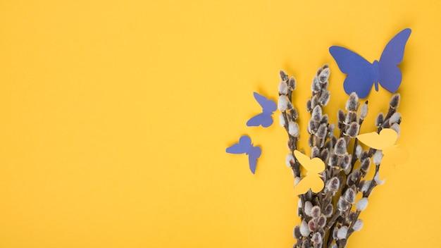 Weidenniederlassungen mit papierschmetterlingen auf gelber tabelle Kostenlose Fotos