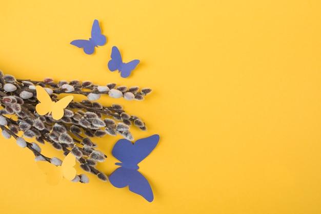 Weidenniederlassungen mit papierschmetterlingen auf tabelle Kostenlose Fotos