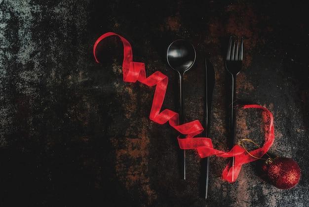 Weihnachten, feierkonzept des neuen jahres, satz tafelsilber auf einem dunklen rostigen, verziert mit rotem band und weihnachtsbaumball, draufsicht copyspace Premium Fotos