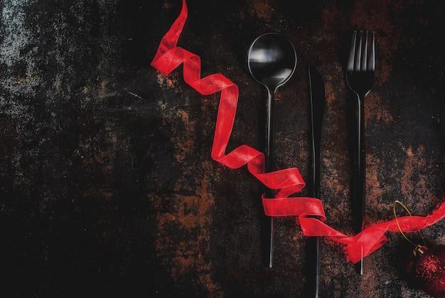 Weihnachten, feierkonzept des neuen jahres, satz tafelsilber auf einer dunklen rostigen szene, verziert mit roter band- und weihnachtsbaumkugel Premium Fotos