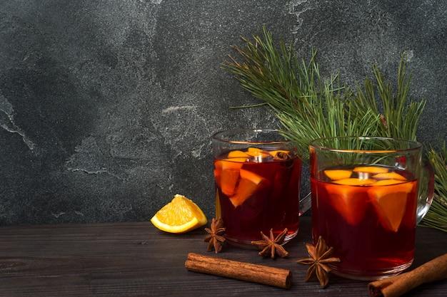 Weihnachten glühte rotwein mit gewürzen und früchten auf einer hölzernen rustikalen tabelle Premium Fotos