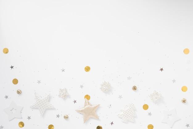 Weihnachten hintergrund. goldene sterne, glocken und bögen auf weißem hintergrund. flache lage, draufsicht, kopienraum Premium Fotos