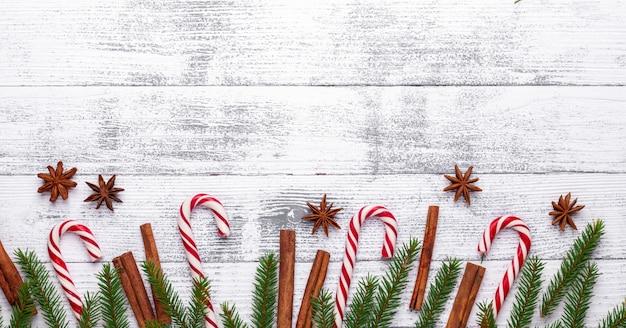 Weihnachten hintergrund. tannenzweige, zuckerstange und geschenke auf einem hellen hölzernen hintergrund. Premium Fotos
