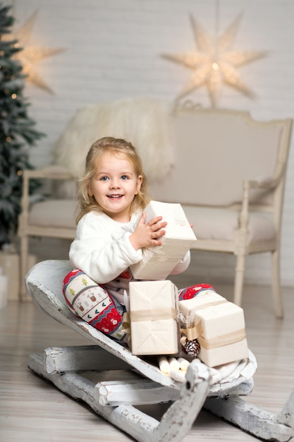 Weihnachten ist schon da. mädchen, das mit weihnachtsgeschenkbox rodelt. kleines nettes mädchen erhielt feriengeschenke. kindergriff-geschenkbox beim rodeln. weihnachten feiern. winteraktivität Premium Fotos