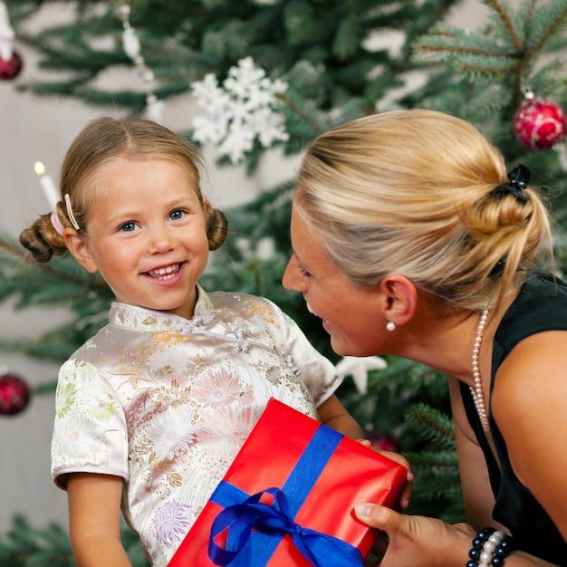 Weihnachten, kind, das ein geschenk empfängt Premium Fotos