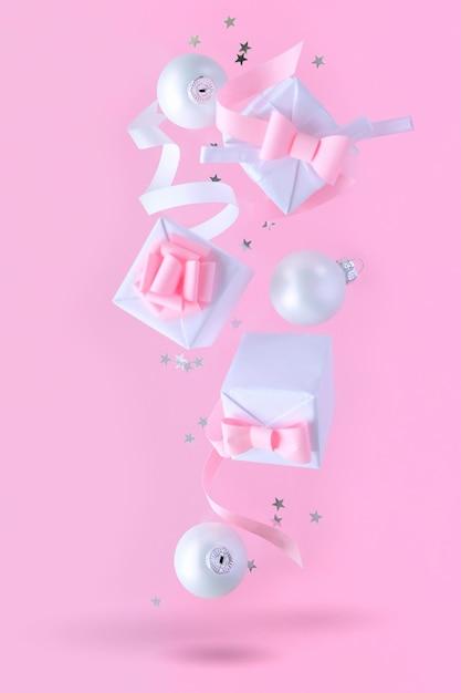 Weihnachten mit dekorationen und geschenkboxen auf rosa hintergrund Premium Fotos