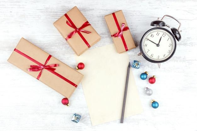 Weihnachten mit geschenkboxen, wecker, weihnachtsdekorationsbällen und blatt papier auf weißem holztisch Premium Fotos