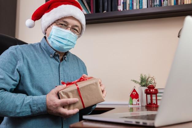Weihnachten online glückwunsch. älterer mann in weihnachtsmannhut und gesichtsmaske gibt ein geschenk und spricht unter verwendung eines laptops für videoanruffreunde und -kinder. weihnachten während des coronavirus. Premium Fotos