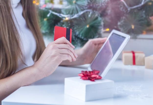 Weihnachten online-shopping. verschwommene frau im weißen pullover kauft weihnachtsgeschenke mit laptop und hält eine kreditkarte Premium Fotos