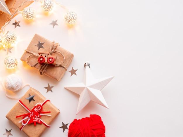 Weihnachten und neujahr diy-geschenke in kraftpapier eingewickelt. geschenk mit rustikalen faden mit spielzeugeisenbahn als dekoration gebunden. Premium Fotos