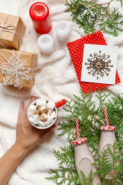 Weihnachten und neujahr festliche gemütliche anordnung, frauenhänden halten eine tasse kakao oder choc Premium Fotos