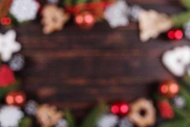 Weihnachten verwischte abstrakten hintergrund, weihnachtsbäume, dekorationen und handgemachte lebkuchenplätzchen auf einem holztisch Premium Fotos