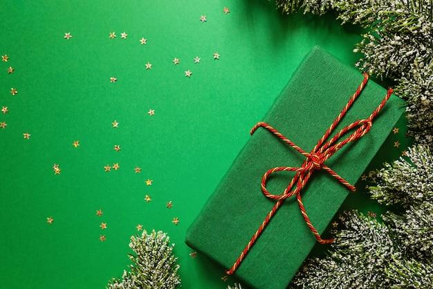 Weihnachten wickelte geschenkbox und baumaste auf grünem hintergrund mit konfettis ein. neues jahr konzept. grußkarte, weihnachtsfeier 2020. flache lage, schablone, draufsicht, kopienraum Premium Fotos