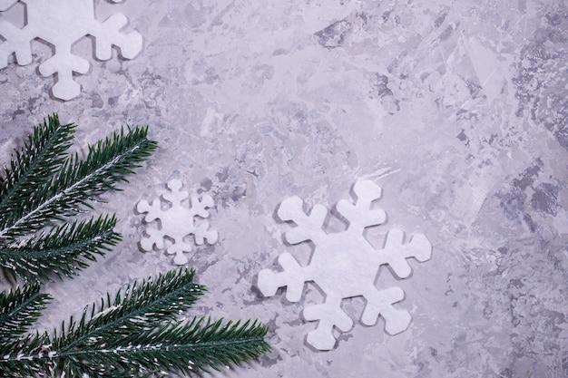 Weihnachten, winter, neujahrskonzept. grauer hintergrund mit weißen schneeflocken und tannenzweigen. flachgelegt, draufsicht Premium Fotos