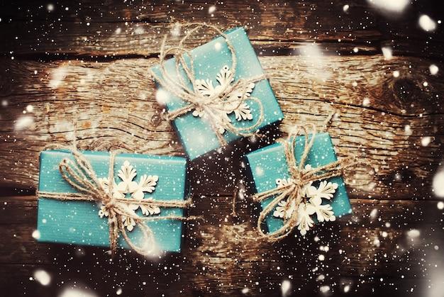 Weihnachts-boxen mit schneeflocken verziert. gezeichneter schnee. dunkel getönt Premium Fotos