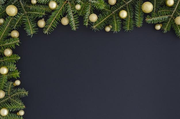 Weihnachts- oder des neuen jahresdekoration: pelzbaumniederlassungen, goldene bälle auf schwarzer hintergrundkopie Premium Fotos