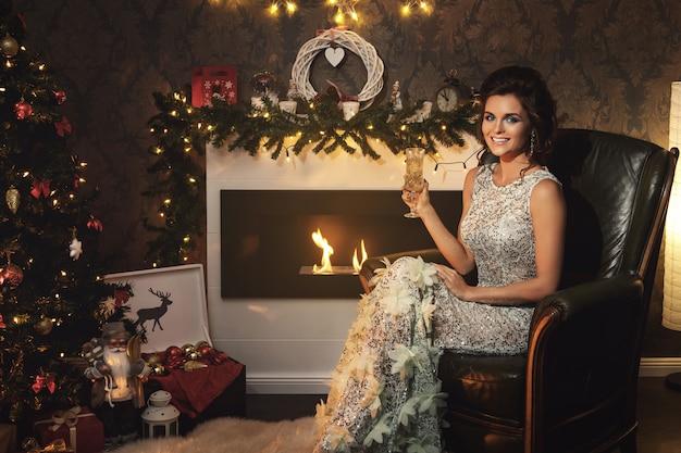 Weihnachts- oder neujahrsfeier. glückliche frau mit einem glas champagner. Premium Fotos
