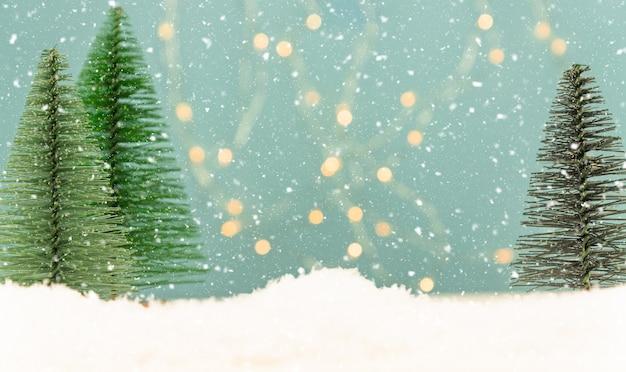 Weihnachts- oder neujahrsgrußkarte mit spielzeugtannen auf blauem bokeh Premium Fotos