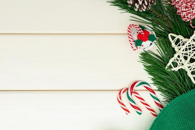 Weihnachts- oder neujahrskomposition auf weißem hölzernem hintergrund. tannenzweige, klingelglocke, zuckerstange Premium Fotos