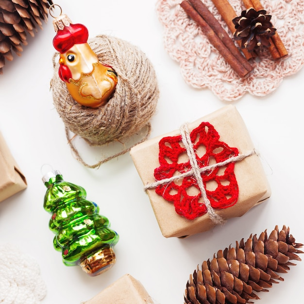 Weihnachts- und neujahrshintergrund mit den handgemachten geschenken eingewickelt im kraftpapier und in den dekorationen. Premium Fotos
