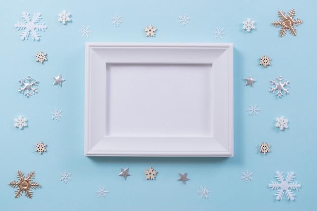 Weihnachts- und winterkonzept. schneeflocke mit fotorahmen auf hellblauem hintergrund. Premium Fotos