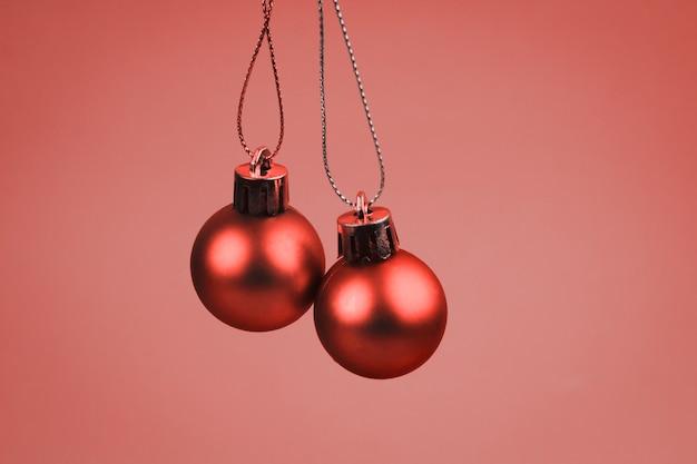 Weihnachtsbälle auf einem vibrierenden hintergrund, lebendes korallenrotes farbmonochrom getont Premium Fotos