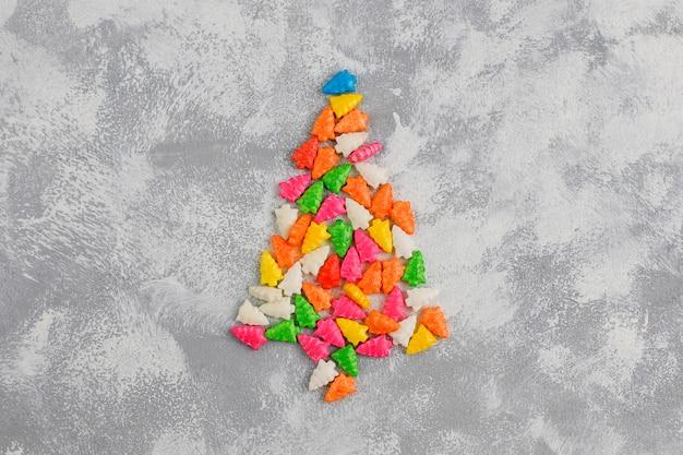 Weihnachtsbaum formte scheinsüßigkeiten auf einer grauen tabelle. draufsicht, flach zu legen Kostenlose Fotos