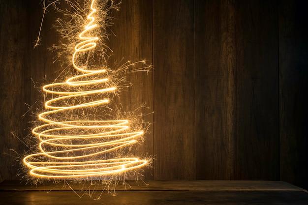 Weihnachtsbaum hergestellt unter verwendung der wunderkerzen mit hölzernem tabellen- und holzwandhintergrund Premium Fotos