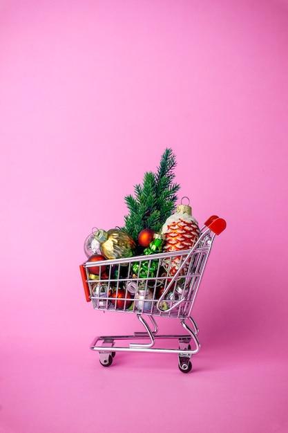 Weihnachtsbaum mit dekorationen in einem supermarktwarenkorb. weihnachtseinkauf und verkaufskonzept Premium Fotos