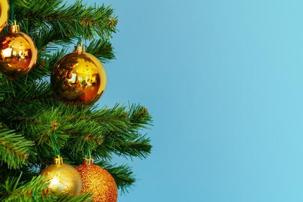 Weihnachtsbaum mit goldenem flitter nah oben auf blauem hintergrund Premium Fotos