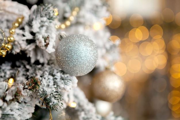 Weihnachtsbaum mit spielwaren und dekorativem schnee für ein guten rutsch ins neue jahr Premium Fotos