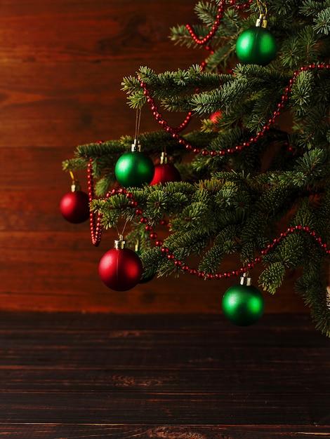Weihnachtsbaum, verkleidet kugeln, steht auf einem holztisch. Premium Fotos