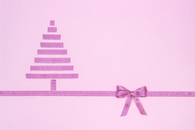 Weihnachtsbaum vom dekorativen glänzenden band mit bogen auf pastellrosa Premium Fotos