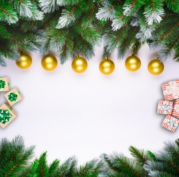Weihnachtsbaumaste auf weißem hintergrund mit weihnachtsrot und goldkugeln Premium Fotos