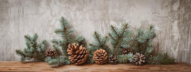 Weihnachtsbaumaste mit kegeln auf einem hölzernen brett gegen eine graue betonmauer. Premium Fotos