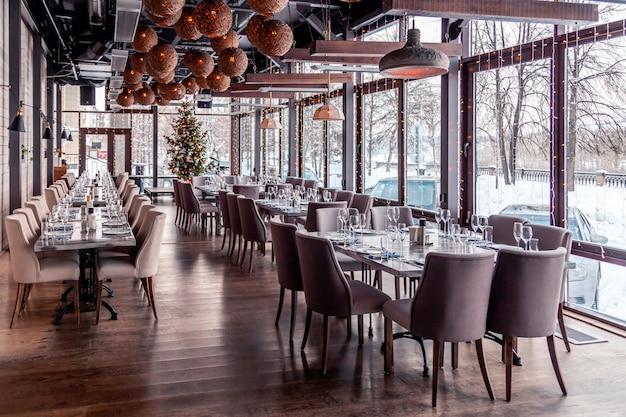 Weihnachtsbeleuchtung, dekor, modernes innenrestaurant, panoramafenster, gedeck, servierbankett, graue textilstühle, serviertische, weinglas, teller, besteck. festliches neues jahr, winter Premium Fotos
