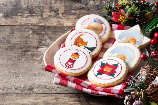 Weihnachtsbutterplätzchen verziert mit weihnachtsgraphiken, auf holztisch copyspace Premium Fotos