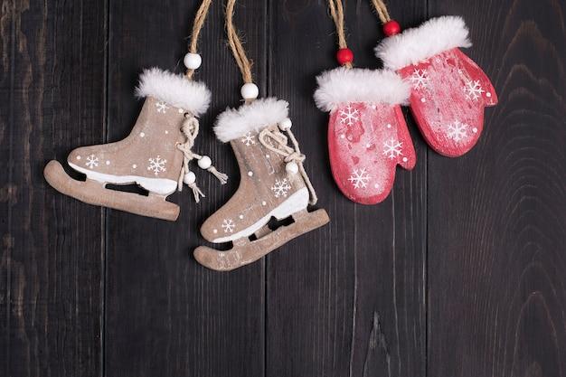 Weihnachtsdekor. schlittschuhe, handschuhe auf einer hölzernen hintergrundebene legen draufsicht Premium Fotos