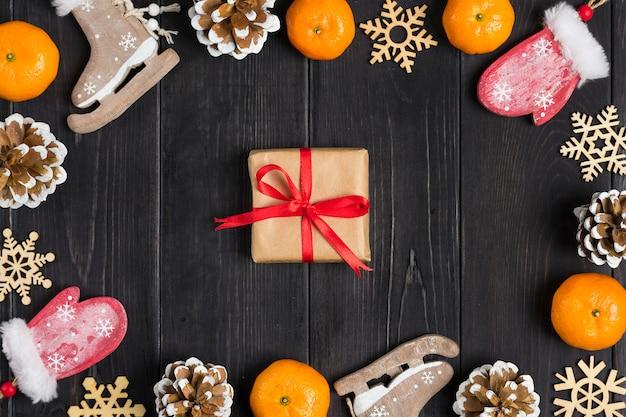 Weihnachtsdekor. Schlittschuhe, Handschuhe, Schneeflocken, Mandarinen, Kegel, Kasten auf hölzernen Hintergrund legen flach Premium Fotos